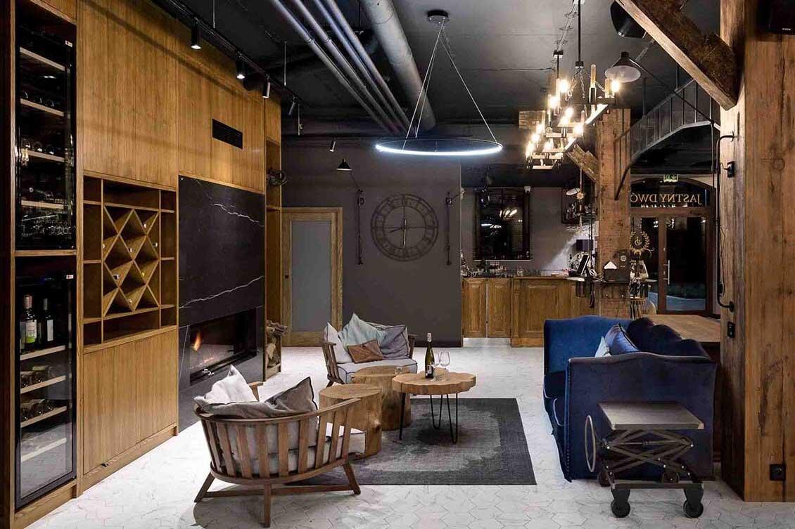 Drewniana zabudowa ściany z półkami na alkohole, dwa wygodne krzesła (może już fotele) i komfortowa sofa, stolik z blatem z drewnianego pieńka i dwa pieńki jako dodatkowe stołki, ponadto stolik na kółkach, a w tle na ścianie duży zegar i drzwi do lokalu