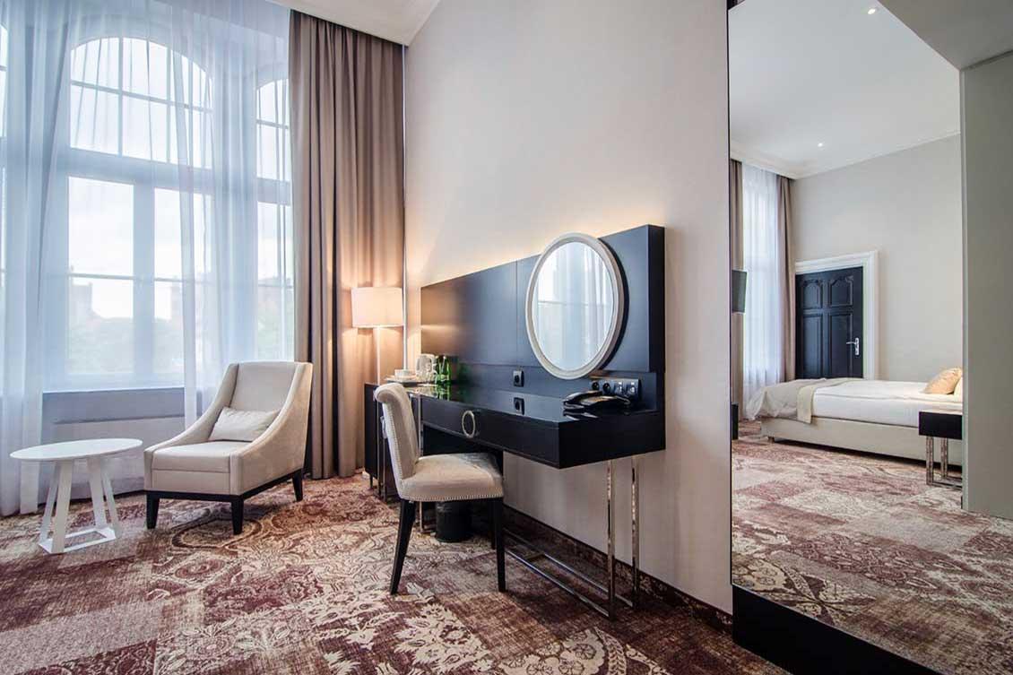 Meble hotelowe (do pokoju hotelowego): czarna konsola przyścienna na metalowych nogach z lustrem, drewniane krzesło, fotel i owalny stolik. Krzesło i fotel mają kremowe obicie i czarne nogi, stolik jest biały. W lustrze szafy przesuwnej odbija się łóżko i drzwi
